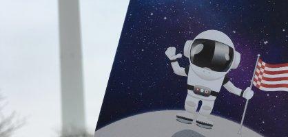 Im Vordergrund ein Flyer mit Sternenhimmel und einer Astronautenperson im Raumfahrtanzug auf dem Mond, hisst die Bremer Speckflagge und winkt in die Kamera, dadrunter ein weißer Text auf rotem Hintergrund: STERNSTUNDEN 2018 Raumfahrtjahr Bremen, Mitmachen, Staunen und Vergnügen. Über 100 Aktionen von Januar bis Oktober