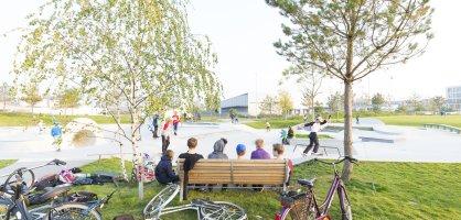 Eine Holzbank von hinten, auf der Personen sitzen mit Blick auf die Rampen eines Skateparks. Drumherum liegen zahlreiche Fahrräder im Gras.