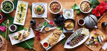 Ein gedeckter Tisch mit unterschiedlichen asiatischen Speisen wie Sushi oder Ente.