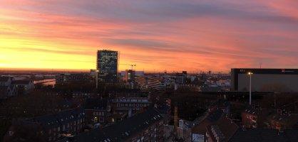 Die Aussicht von oben auf eine Straße und Häuser vor einem pink gefärbtem Himmel.