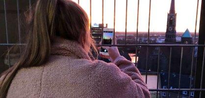 Eine Person hält ihr Smartphone durch ein Gitter und fotografiert die Aussicht von oben auf darunterliegende Gebäude.