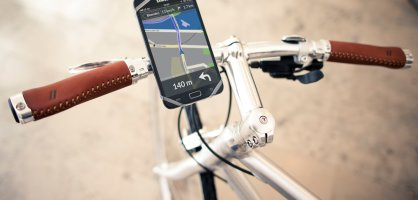 Fahrradlenker mit Smartphone an der Halterung namens Finn, das eine Fahrrad-App zeigt.