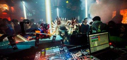 Eine Frau mit Indianerkostüm streckt ihre Arme in Richtung des DJ Pults.