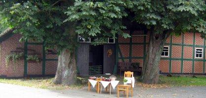 Ein kleiner Verkaufsstand vor einem rotgeklinkerten Bauernhof