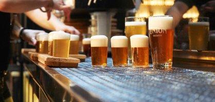 Frisch gezapfte Biere unter einer Reihe Zapfhähne