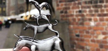 Eine Hand, die eine Metallfigur der Bremer Stadtmusikanten vor die echte Bronzefigur der Bremer Stadtmusikanten hält.