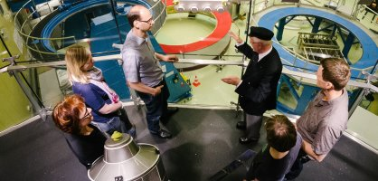 Eine Gruppe Besucher*innen wird durch Räumlichkeiten bei Airbus geführt.