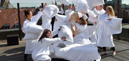 Fröhliche Menschen in weißen Bademänteln machen auf einer Dachterrasse eine Kissenschlacht.