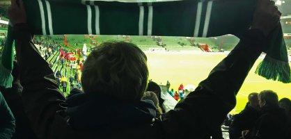 Eine Frau mit Werder-Schal in der Ostkurve des Weser-Stadions