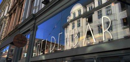 In einem Fenster mit der Aufschrift Heldenbar spiegeln sich die benachbarten Häuser.