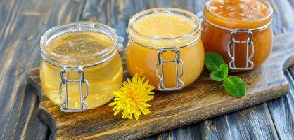 Verschiedene Honigsorten in drei Honiggläsern.