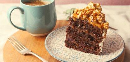 Ein Stück Kuchen und eine Tasse Kaffee auf einem Holzbrettchen