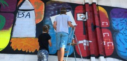 """Zwei Teenager sprühen ein A des Wortes """"Artspace""""."""