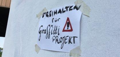 """Ein Zettel mit dem Schriftzug """"Freihalten für Graffitti Projekt"""" klebt auf einer weißen Wand."""