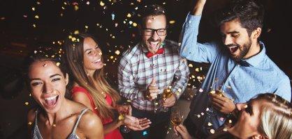 Eine Gruppe von Männern und Frauen schmeißen Konfetti in die Luft und halten Sektgläser