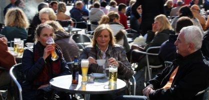 DreiPersonen sitzen auf dem Marktplatz und trinken ein Bier