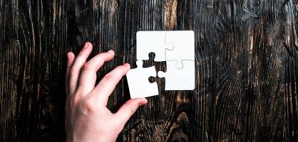 Eine Hand ergänzt ein letztes Puzzleteil zu einem Puzzle, das ein Rechteck formt.