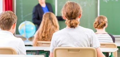 ein Lehrer steht an einer Tafel vor einer Schulklasse