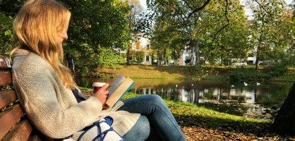 Eine junge Frau sitzt in den herbstlichen Wall-Anlagen auf einer Parkbank, liest ein Buch und trinkt einen Kaffee