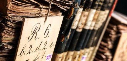 Gestapelte Dokumente und aneinander gereihte Buchrücken in einem Regal.