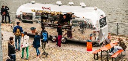 Ein silberner Foodtruck steht in einer Stadt.