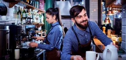 Ein Student und eine Studentin Kellnern in einem Café