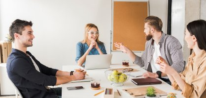Zwei Frauen und zwei Männer sitzen bei einer Teambesprechung am Bürotisch.
