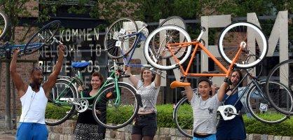 Eine Gruppe von Menschen hält ihre Fahrräder hoch.