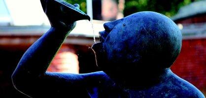 Skulptur zeigt Männerbüste mit zum Mund geführter Schale aus der Wasser fließt