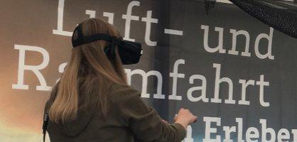 """Ein Mädchen hat eine VR-Brille auf. Hinter ihr stehen die Worte """"Luft- und Raumfahrt erleben"""""""