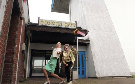 Zwei Frauen, verkleidet im Retro-Look, posieren und schwingen eine Fahne vor dem Eingang der Golden City.