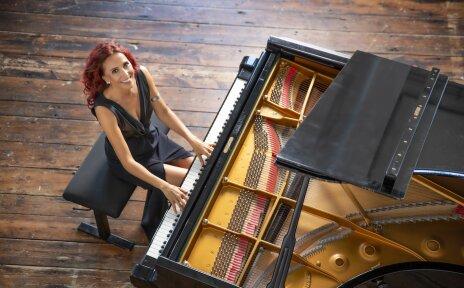 EIne Frau mit roten Haaren sitzt in einem schwarzen Kleid an einem Klavier.