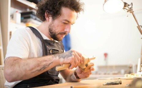 Zu sehen ist ein Mann. Er arbeitet mit Holz und trägt eine schwarze Latzhose.