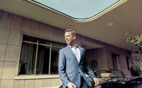 Tom Gaebel trägt einen blauen Anzug und steht vor einem Cabrio. Im Hintergrund ist der Eingang eines Hauses.