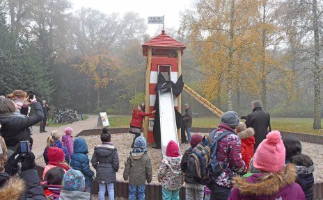"""Auf dem Bild ist ein Spielplatz in einem Park zu sehen. Senatorin Anja Stahmann enthüllt ein Spielgerät in Form eines Leuchtturms. Im Publikum sind viele Kinder zu sehen. Das Spielgerät ist mit Klettermöglichkeiten und Rutsche ausgestattet. Auf dem Dach befindet sich eine Fahne mit der Aufschrift """"Platz der Kinderrechte""""."""