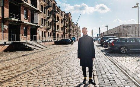 Dennis Paul steht auf der Straße vor der Hochschule für Künste in Bremen
