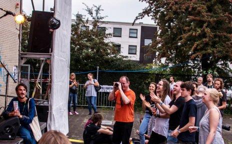 Menschen jubeln vor einer Bühne.