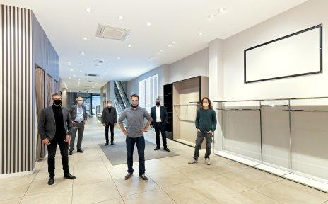 Gewinner des Concept-Store Wettbewerbs und Beteiligten des Projektes stehen in der neuen Ladenfläche mit Abstand zueinander und tragen Masken.