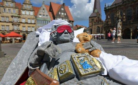 Eine als Roland verkleidete Person legt sich mit Schlafmütze, Schlafbrille und Teddy auf dem Marktplatz zur Ruhe