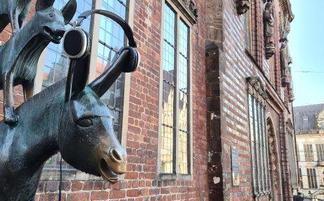 Der Esel der Statue der Bremer Stadtmusikanten trägt Kopfhörer. Darüber ist noch der Hund zu sehen