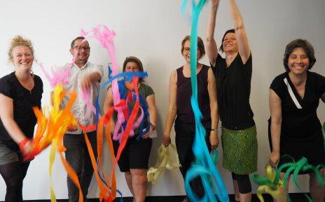 Fünf Frauen und ein Mann aus dem Team des Kinderschutz-Zentrums. Sie werfen lachend bunte Papierschlangen in die Luft.