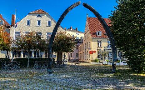 Ein kleiner Platz wird von einem Bogen geziert. Dahinter stehen kleine Fachwerkhäuser.