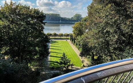 Von einer Aussichtsplattform kann man über einen Park gucken. Im Hintergrund ist die Weser zu sehen.