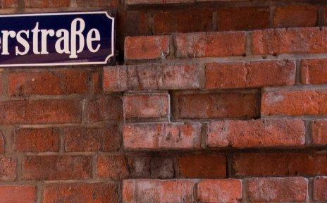 Das Straßenschild der Böttcherstraße ist dunkelblau mit weißer Schrift und an einer roten Backsteinwand angebracht.
