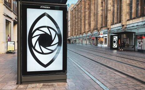 An einer Haltestelle ist an einer Leuchtreklame das Logo des Hochkantfilmfestivals zu sehen.