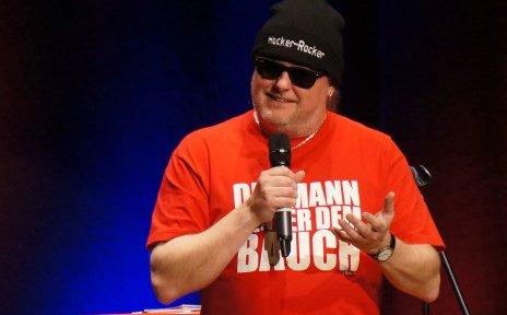 Markus Krebs mit Mütze und Sonnenbrille auf einer Bühne.