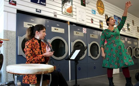 Eine Flötistin und eine Geschichtenerzählerin haben einen Auftritt in einem Waschsalon.
