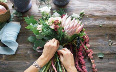 Frauenhände binden einen bunten Blumenstrauß zusammen.