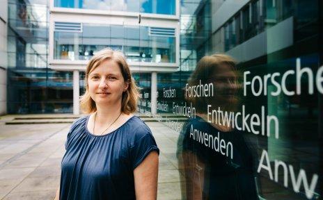 Eine Frau schaut in die Kamera vor einer Glaswand in die Kamera; Quelle: WFB/Jonas Ginter