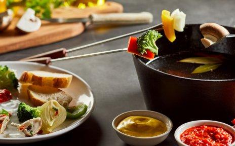 Ein Fonduetöpf mit Tellern voller verschiedener Gemüsearten und Saucen